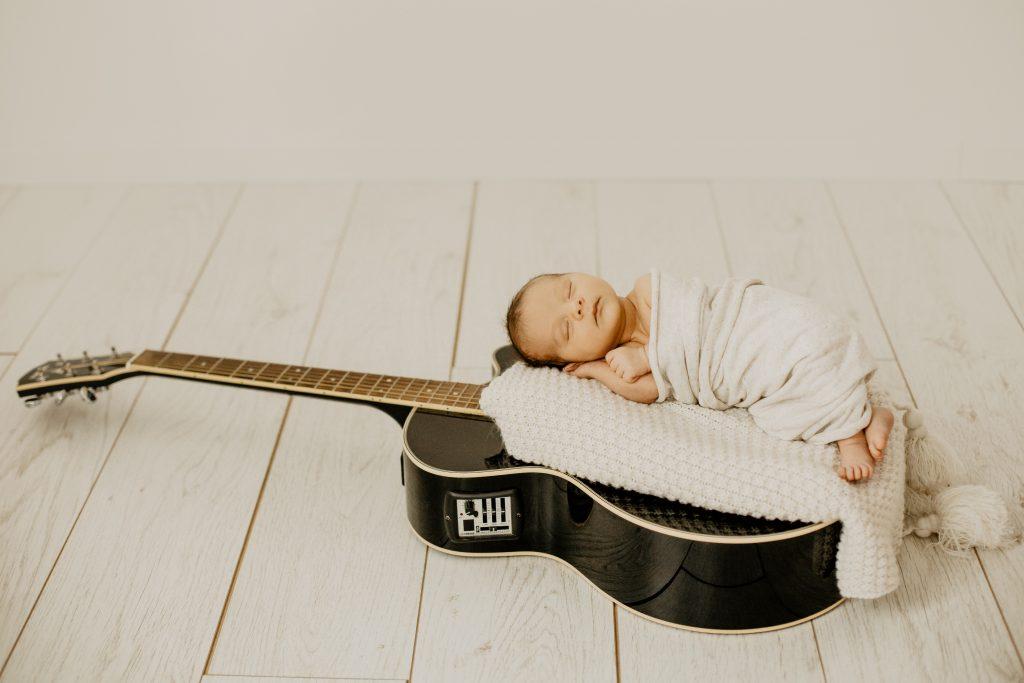 Séance naissance en studio à Croix dans le Nord avec les parents et une guitare