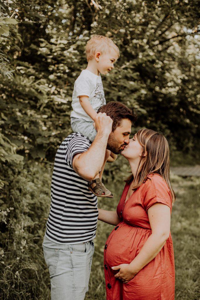 Séance photo en famille avec un bisou en extérieur